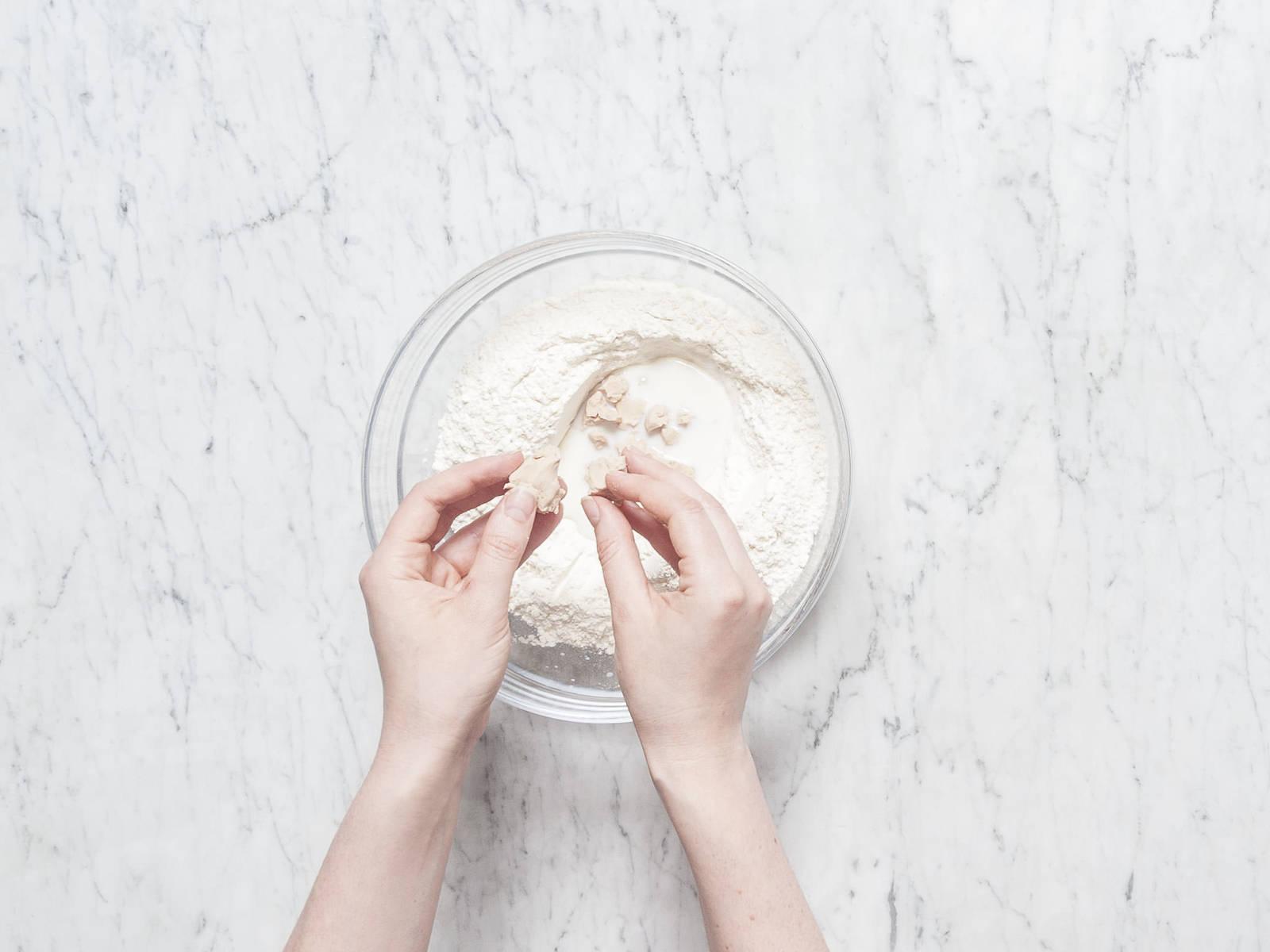 将面粉和泡打粉放到一个搅拌碗中,搅拌混合。在其中间搅出一个小洞,倒入牛奶。将新鲜酵母捏碎,撒到牛奶中。撒上些许糖,慢慢开始和面,直至形成面团。用厨房纸盖住碗,放到温和处,让面团发酵15分钟。