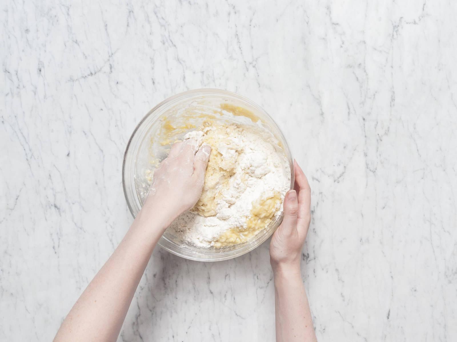 在小平底锅中融化些许黄油,放凉至室温。撕开香草豆荚,挖出籽。面团发酵好后,打入鸡蛋,放入剩余的糖、融化好的黄油、酪乳、些许牛奶、盐和半份香草籽,搅拌均匀。用手将面团揉至软滑。撒上面粉,放回碗中,盖好厨房纸,再次让其在温和出发酵60分钟。