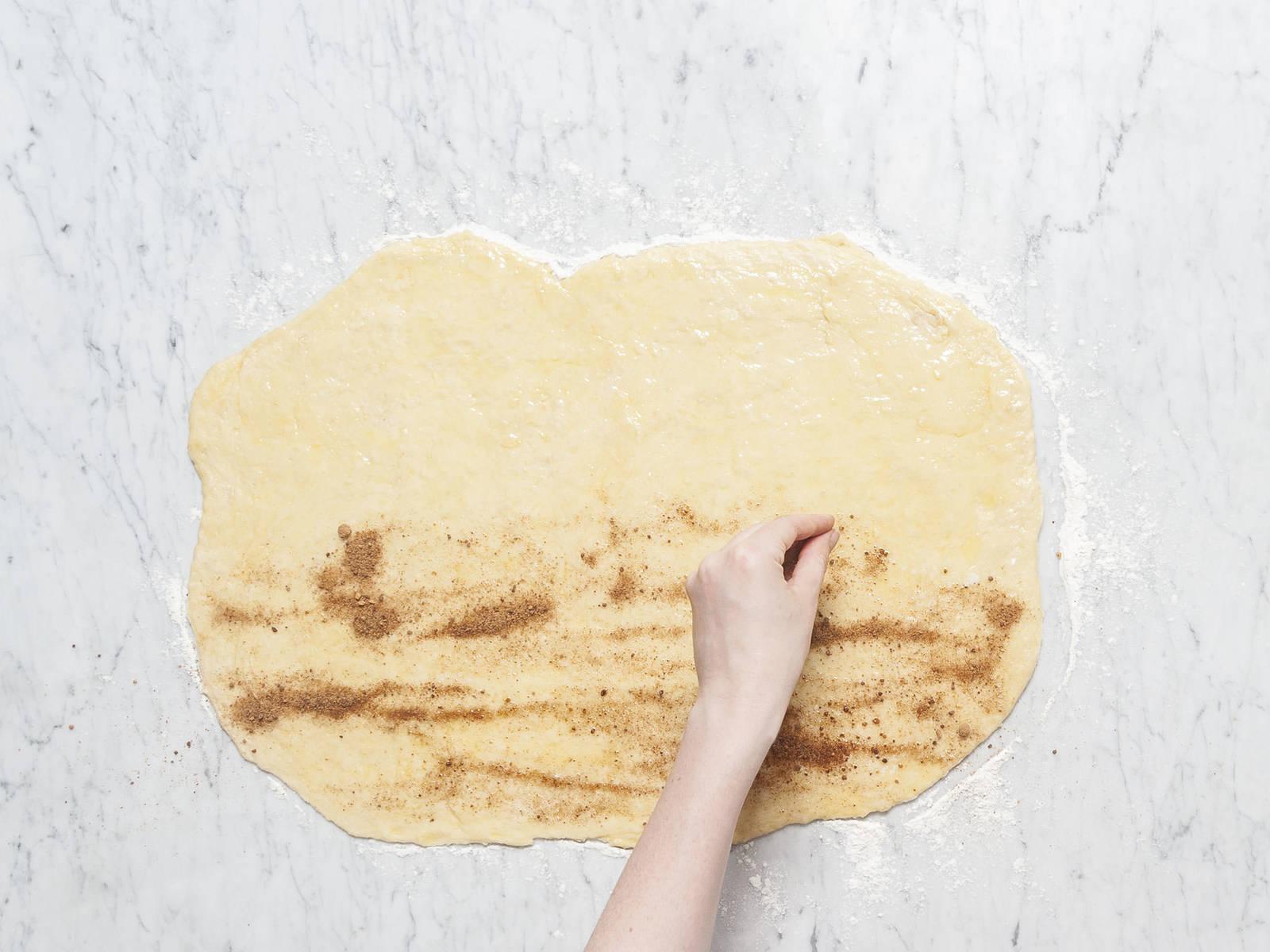 用黄油润滑烤盘。将蔗糖和肉桂放入小碗中,搅拌混合。往工作台上撒些面粉,将面团擀成约7毫米厚的长方形。在小平底锅中融化剩余的黄油,然后均匀涂抹到面团上。撒上肉桂糖。