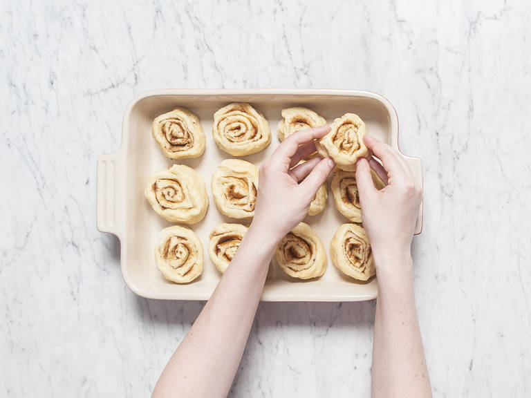 Roll up the dough like a carpet, starting from the long end. Cut the roll crosswise into equal-sized pieces, each approx. 3-cm/1-inch thick. Transfer into greased baking pan. Cover with a kitchen towel and let rise in a warm place for approx. 90 min.