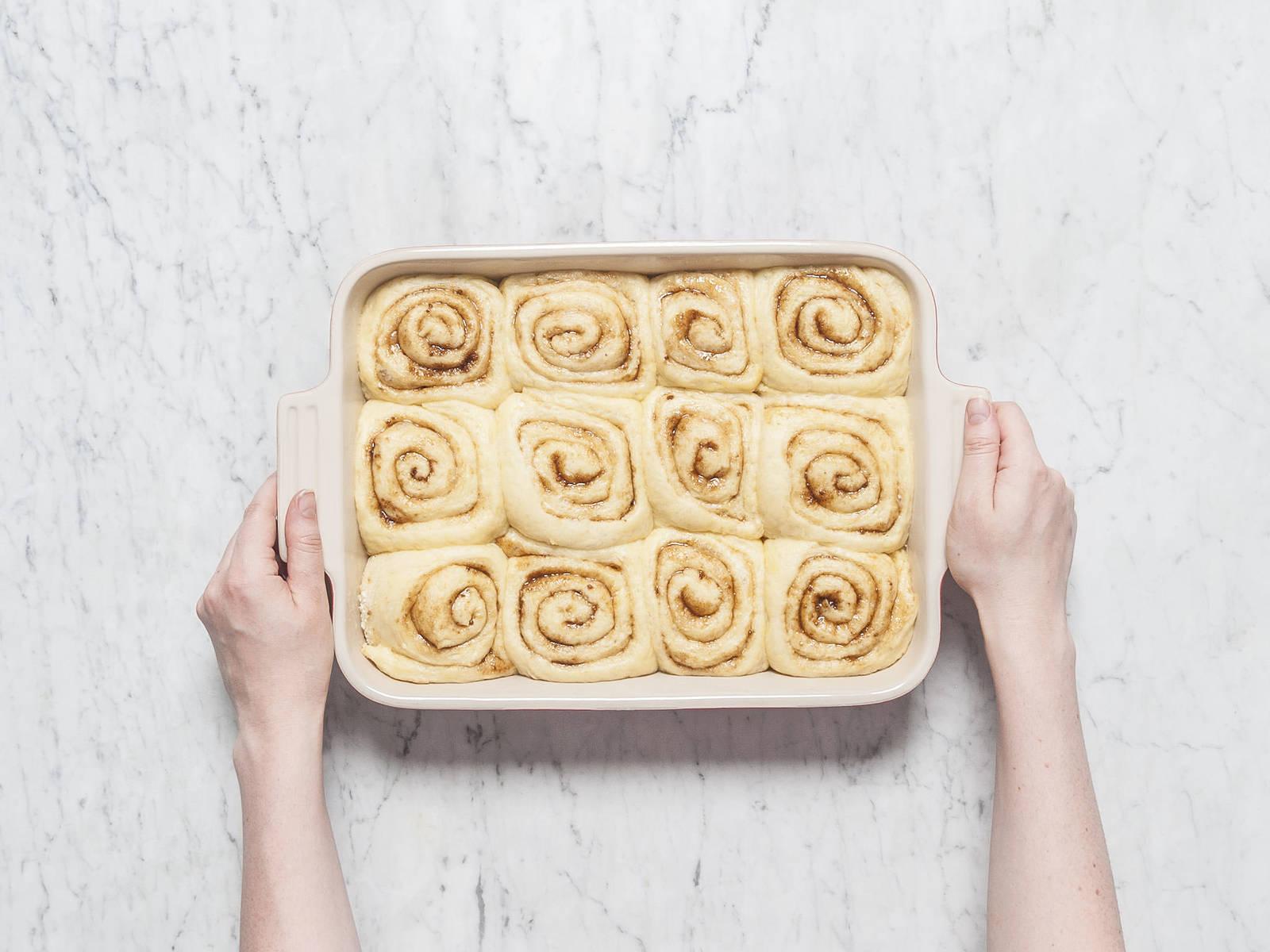 在发酵的同时,将烤箱预热至170℃。放入肉桂卷,烤25分钟,或直至它们变得金黄。从烤箱中取出,放凉10分钟。