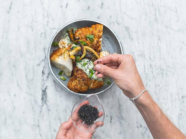 Sobald der Blumenkohl gebacken ist, vierteln und mit Joghurtdip und gerösteten Blumenkohlblättern servieren. Mit restlichen Frühlingszwiebeln und schwarzem Sesam bestreuen. Guten Appetit!