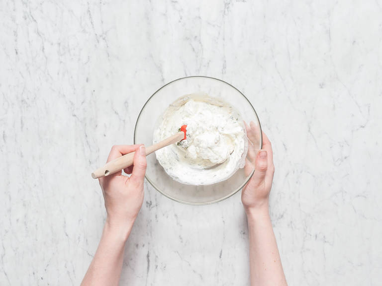 For the dip, peel and chop garlic finely. Chop thyme and mint. Add cream cheese and sour cream to a mixing bowl and stir in lemon juice, garlic, thyme, and mint. Season with salt and pepper and set aside.