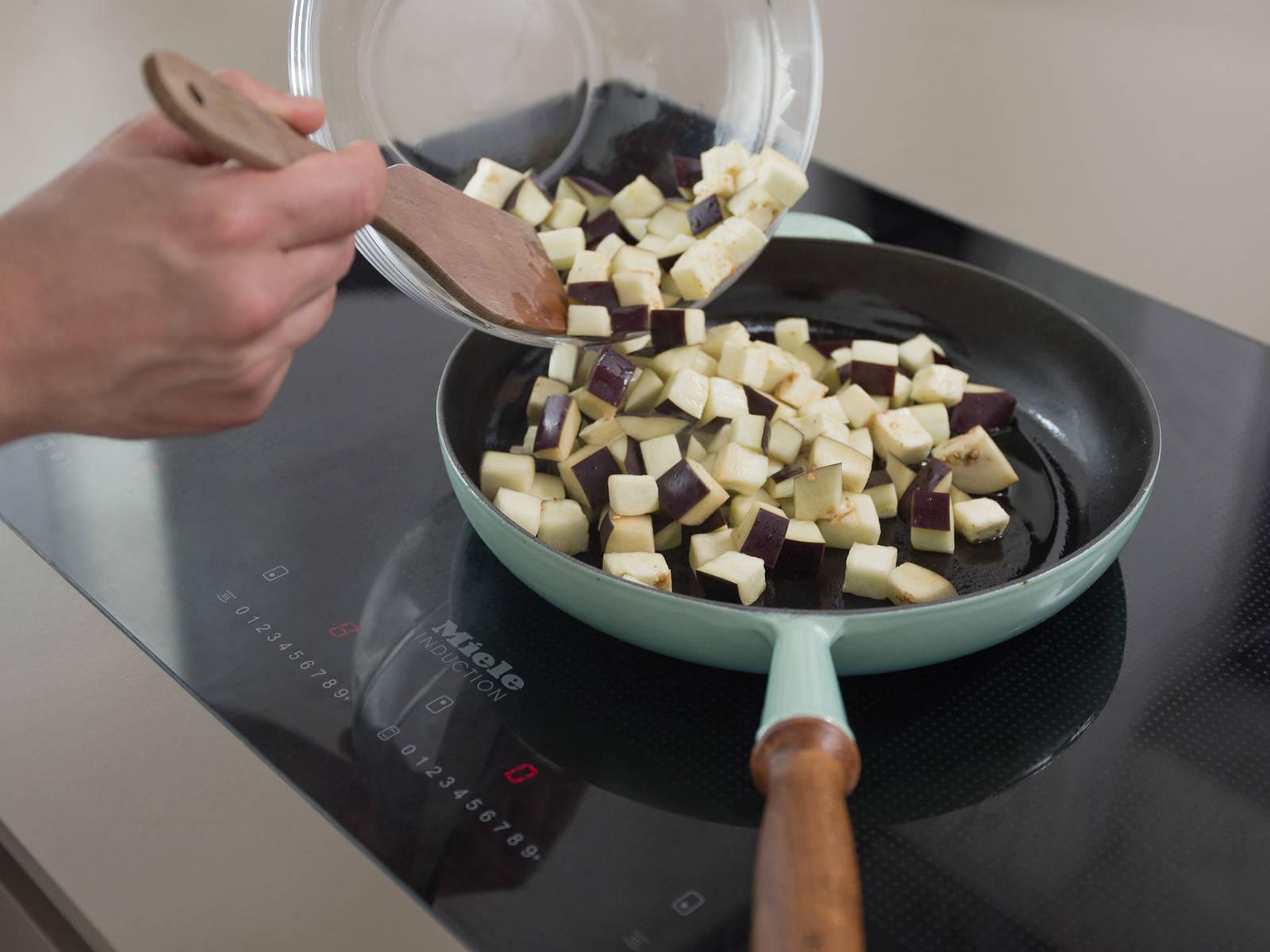 Auberginenwürfel mit klarem Wasser abspülen und trocken tupfen. Olivenöl in einer Pfanne bei hoher Hitze erwärmen und Aubergine darin ca. 3 - 4 Min. scharf anbraten.
