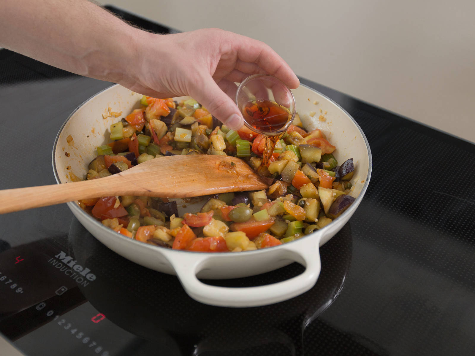 Transfer eggplant to the other pan and stir to combine with the other vegetables. Add red wine vinegar and let it simmer for approx. 10 min. Season with salt and pepper and serve with freshly chopped basil, toasted pine nuts, and olives. Enjoy!