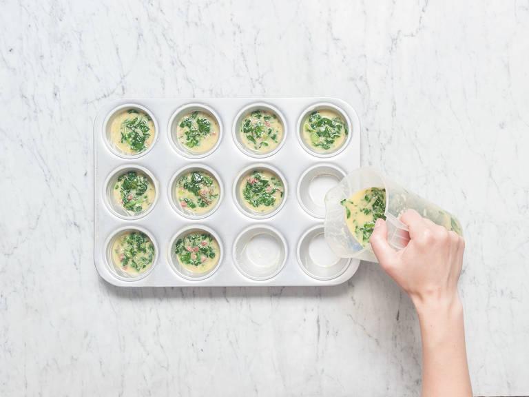 将菠菜混合物和帕马森干酪屑放入鸡蛋混合物中,搅拌均匀。用黄油润滑玛芬杯,勺入混合物。
