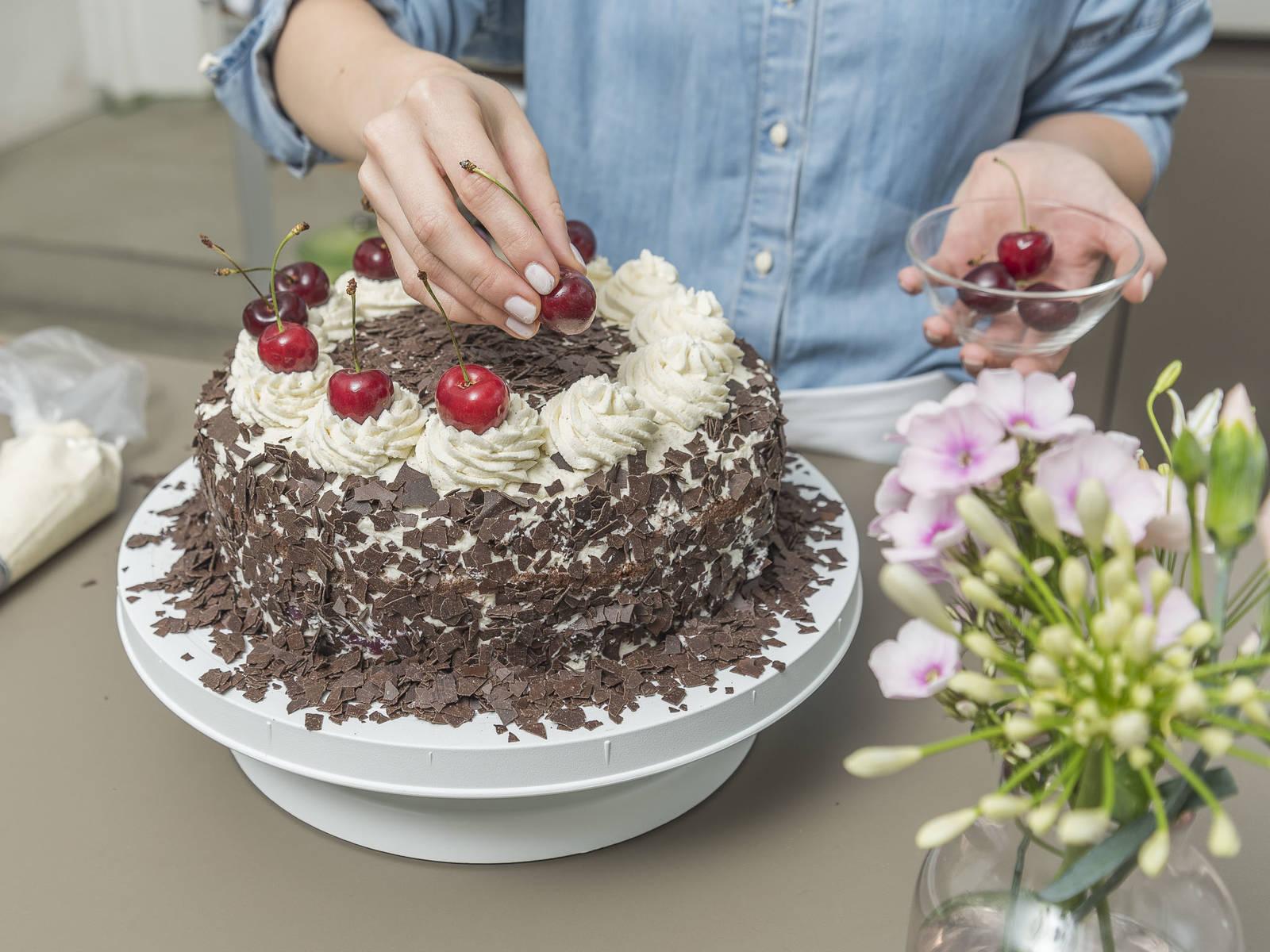 要完成蛋糕顶层,先在碗中加入剩余的奶油、塔塔粉和香草糖,搅打至硬性发泡,倒入带星型裱花嘴的裱花袋中。用生奶油涂满整个蛋糕,在侧面装饰上巧克力屑,也在顶部装饰上一圈巧克力,在边缘处均匀地裱上12个星型奶油花,在上面分别点缀一颗樱桃,冷藏2小时后就可以享用啦!