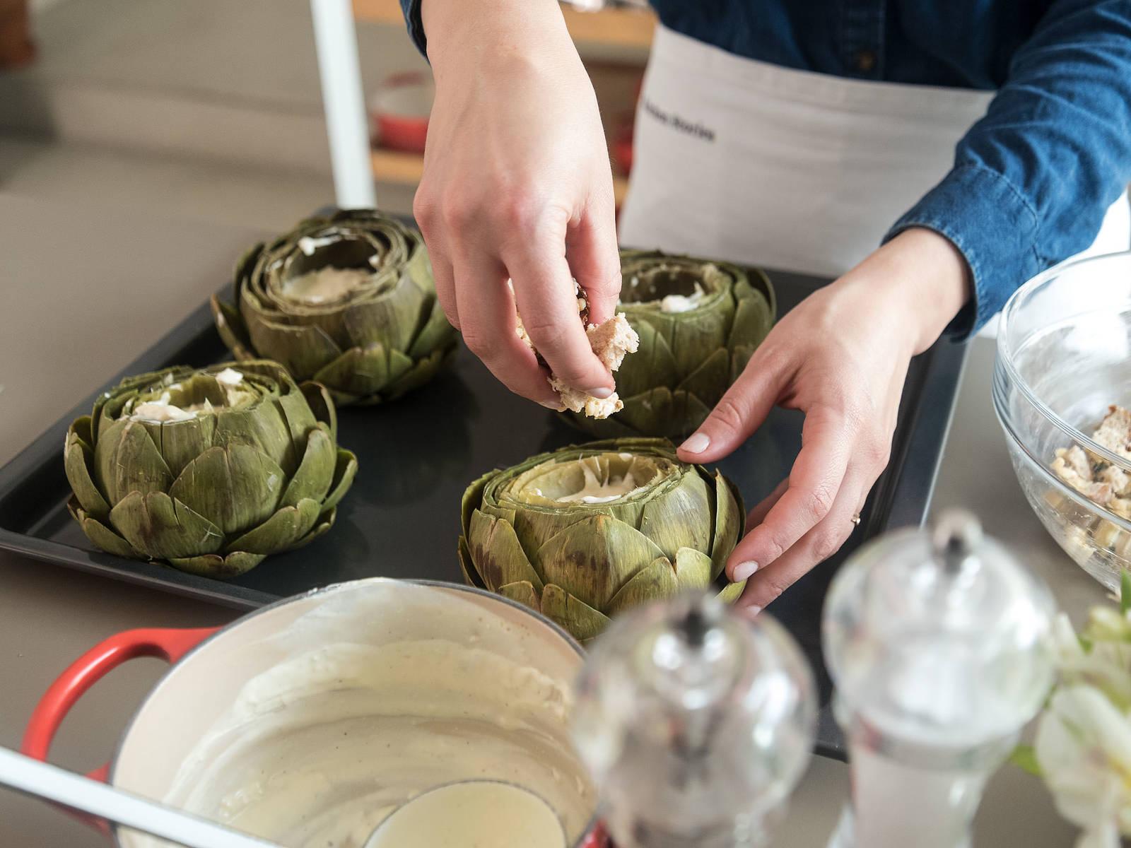 将洋蓟中间的多毛部分和紫色刺叶挖出。把洋蓟放到烤盘中,将奶酪酱放到中间部分,填满一半。均匀撒上面包丁混合物。