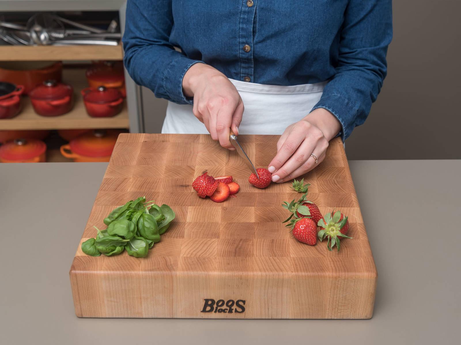 将烤箱预热至190℃。草莓去头后切成圆片。将罗勒叶细细切成长丝。