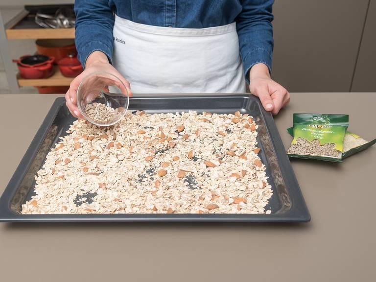 Mandeln grob hacken und mit Haferflocken, Leinsamen und gemischten Nüssen und Samen auf einem Backblech verteilen. Ca. 12 Min. auf der mittleren Schiene bei 180°C goldbraun rösten.