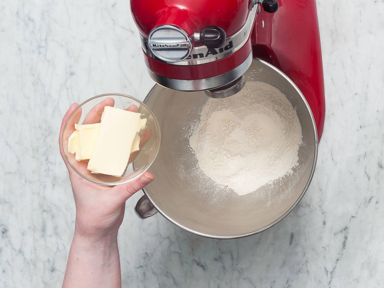 将面粉和泡打粉放到搅拌碗或立式搅拌机的碗中,混合均匀。加入黄油,搅拌混合,直至形成有着小疙瘩的面团。