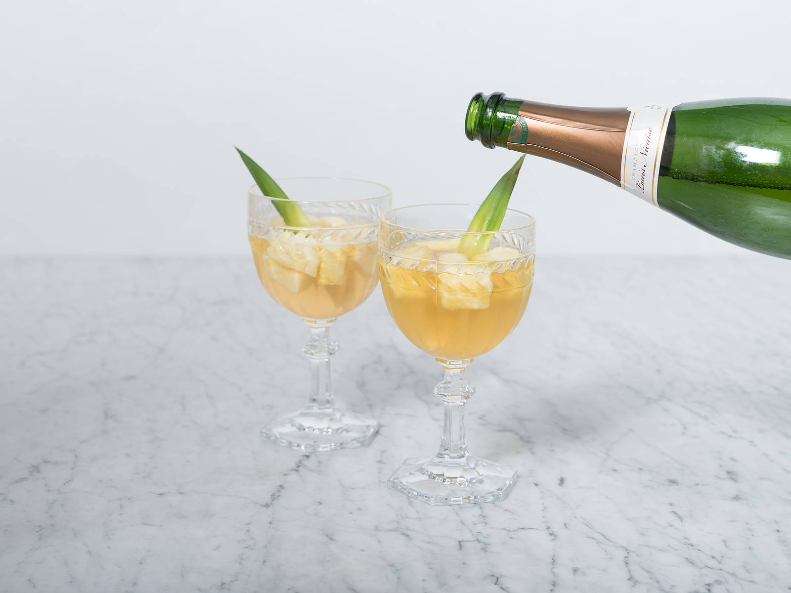 Serve in stemmed glasses, top with Champagne, and garnish with berries and pineapple leaves.  Enjoy!