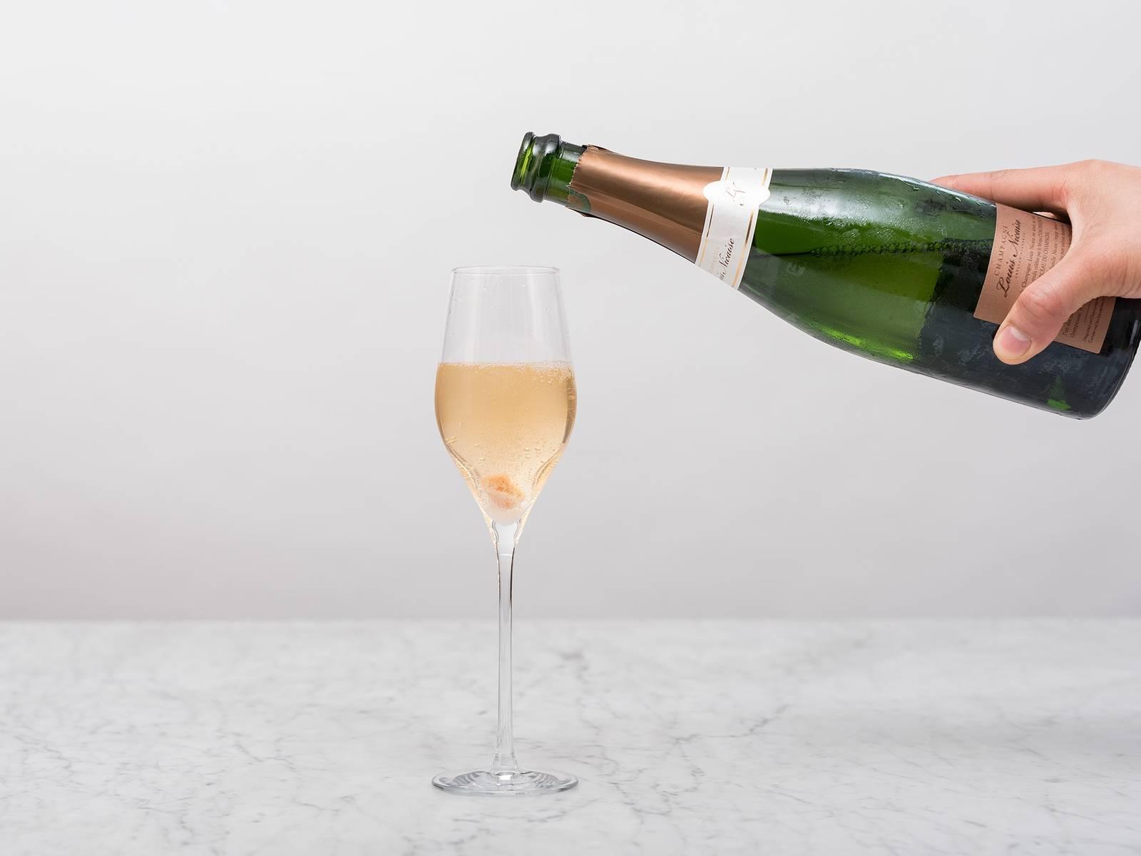 将糖放到杯中,倒满香槟。
