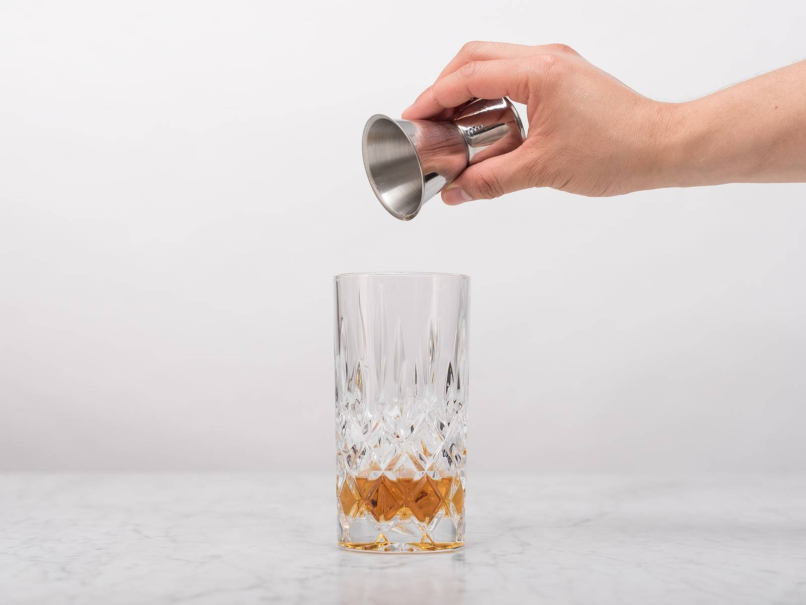 Pour whiskey into a highball glass.