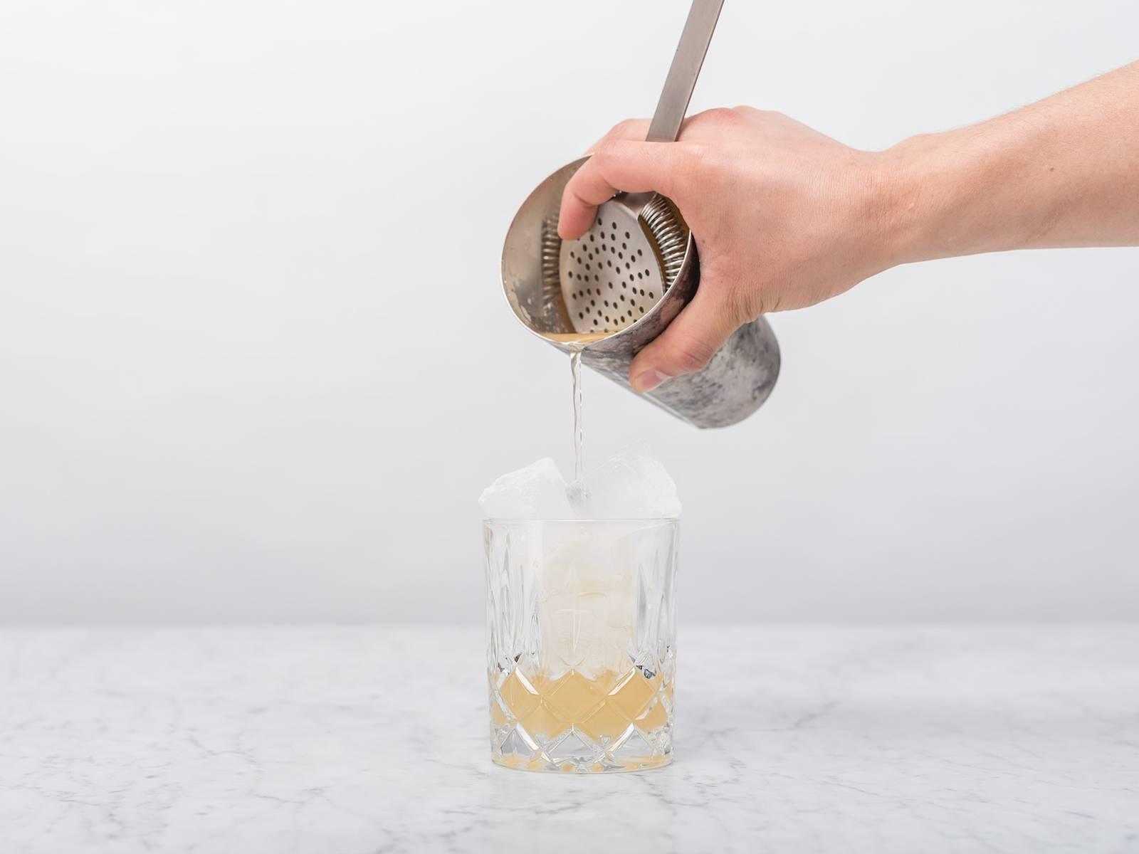 Den Cocktailshaker kräftig schütteln. Eiswürfel in ein Trinkglas füllen und den Cocktail aus dem Shaker ins Glas seihen.