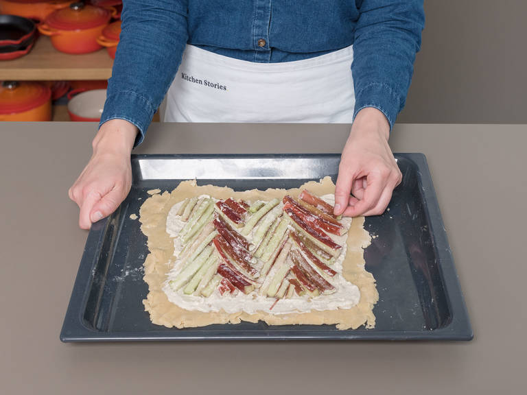 Arrange the rhubarb in a chevron pattern over the mascarpone cheese filling; cut the rhubarb as necessary to fit. Fold the edges of the dough over the rhubarb and crimp. Beat egg yolk into a bowl and brush the dough with it.