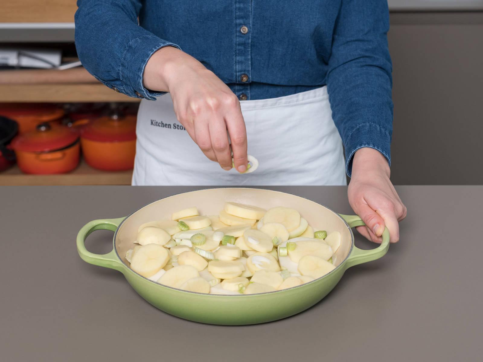 Eine große Auflaufform mit Butter einfetten. Einen Teil der geschnittenen Zwiebeln und Frühlingszwiebeln hineinlegen und eine Schicht Kartoffel- und Kohlrabischeiben darauf verteilen. Direkt eine zweite Schicht darüber legen. Für die dritte Schicht erneut Zwiebel und Frühlingszwiebel dazugeben. Anschließend den Schinken und einen Teil des Emmentalers und der Haferflocken darauf verteilen. Die restlichen Kartoffel- und Kohlrabischeiben darauflegen.
