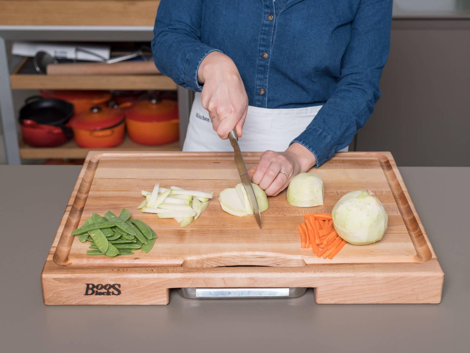 将部分胡萝卜和苤蓝削皮,切片,然后切成小条。解冻毛豆。清洗蜜豆,切去底部,撕掉连着的边丝。将芝麻烘烤至散发香气。