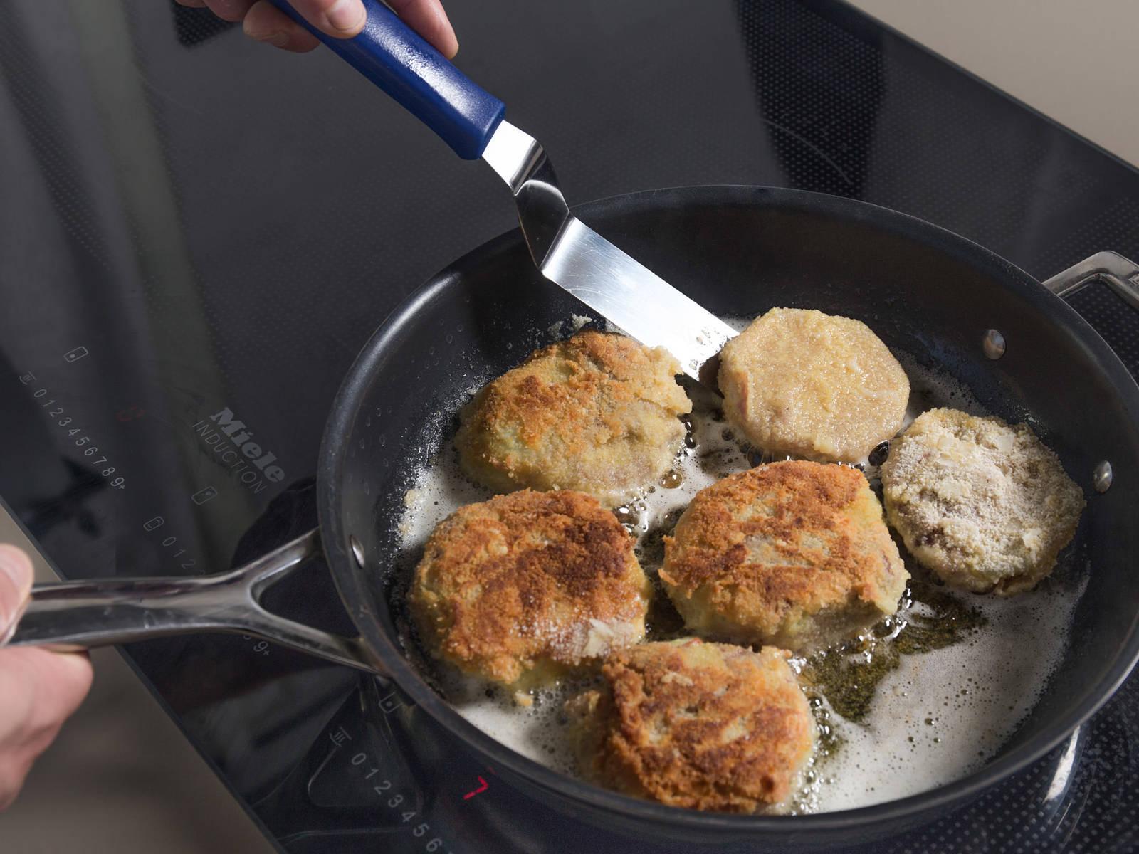 在煎锅中,中高火加热澄清黄油和植物油。放入苤蓝片,每面炸5分钟或直至苤蓝片变棕色。放到铺好厨房纸的盘中吸干多余油分。搭配青酱享用。祝好胃口!