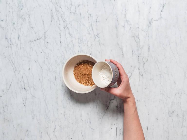 桃子切半,去核后置于一旁。往一个碗中放入杏仁碎、红糖、面粉、盐、冷黄油,搅拌至形成大的松散碎块。