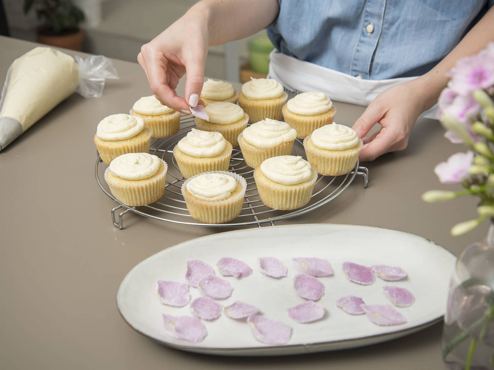 Frost the cupcakes by working your way from inside out, drawing upwards in circles. Decorate each cupcake with a sugarcoated rose petal. Enjoy!