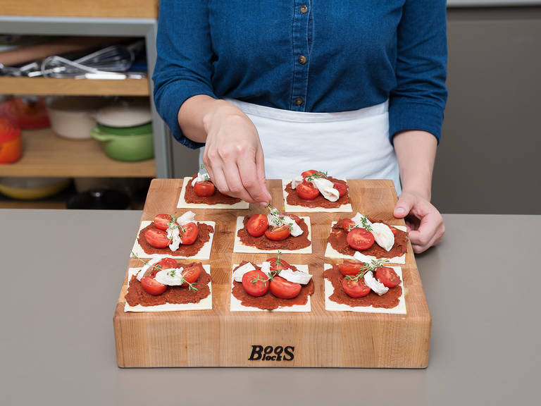 Whisk the egg yolk and lightly brush the edges of the puff pastry with it. Place a spoonful of tomato paste mixture onto each piece of pastry and spread it to the edges. Arrange goat cheese and tomatoes on each tart and garnish with a sprig of thyme. Transfer tartlets to baking sheet.