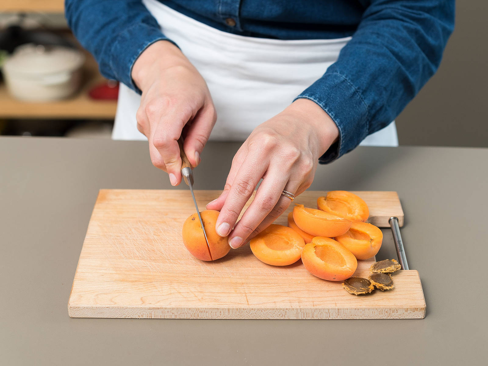 Preheat oven to 200°C/400°F, and grease the tart pan. Melt butter in a small pot over low heat, and set aside to cool. Wash apricots and dry, remove pit with a sharp knife, and cut in halves.