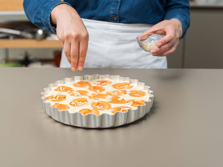 Pour the batter into the greased pan and spread the apricot halves evenly on top, with the cut side-up. Sprinkle with vanilla sugar and almonds.
