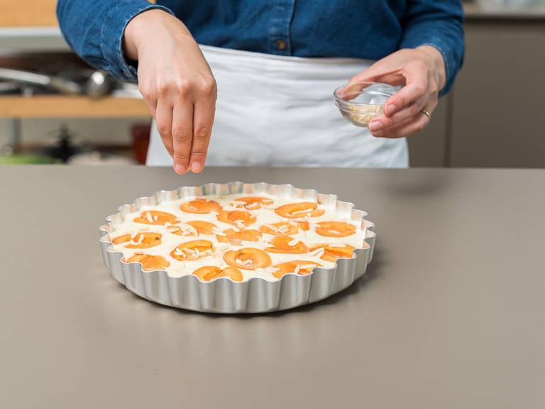 Teig in die eingefettete Tarteform gießen und die Aprikosenhälften mit der offenen Seite nach oben gleichmäßig darauf verteilen. Mit Vanillezucker und Mandelsplittern bestreuen.