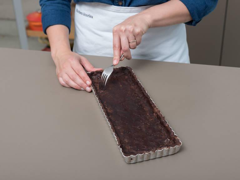 将烤箱预热到180°C,然后在塔吉锅上摸上油。将面团擀平然后压入锅中。用叉子在面团上戳出些小洞,用烘焙纸覆盖,然后在派盘表面填满陶瓷烘焙豆来压住面团。将其转移到提前预热的烤箱,以180°C烘烤将近20分钟。