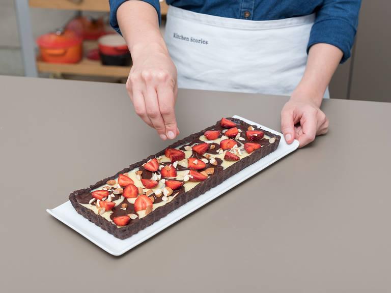 Währenddessen Erdbeeren waschen und schneiden. Erdbeeren auf die Schokoladen-Tarte geben und mit gehackten Mandeln bestreuen. Zurück in den Kühlschrank stellen und ca. 1 Std. ruhen lassen. Guten Appetit!