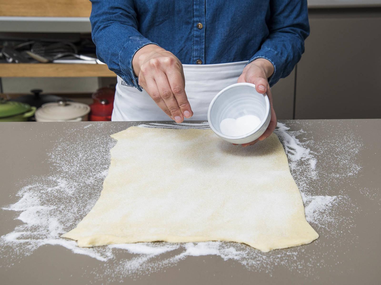 将糖和盐放到小碗中混合,然后撒一些到干净的工作台上,放上酥皮。将酥皮擀成长方形,约0.5厘米厚。压一压酥皮,让底下的糖都嵌进去。撒上剩余的糖盐,用擀面杖稍微擀压,把颗粒压进酥皮中。