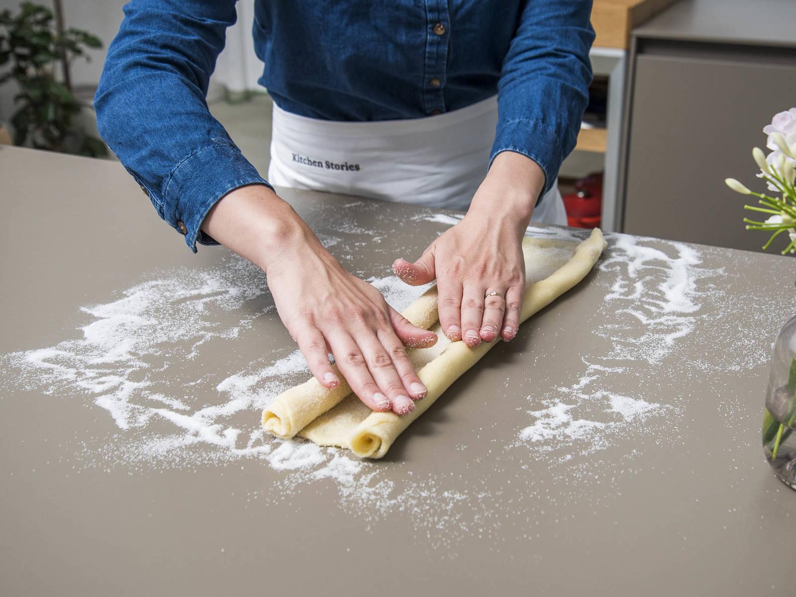 从酥皮长的一边将其紧实地卷起一半。换一边,再卷起一半,使两个卷面在中间相接。小心地沿着相接处压一压酥皮,以让其接得更紧一些。然后,用塑料膜裹好,冷藏30分钟。