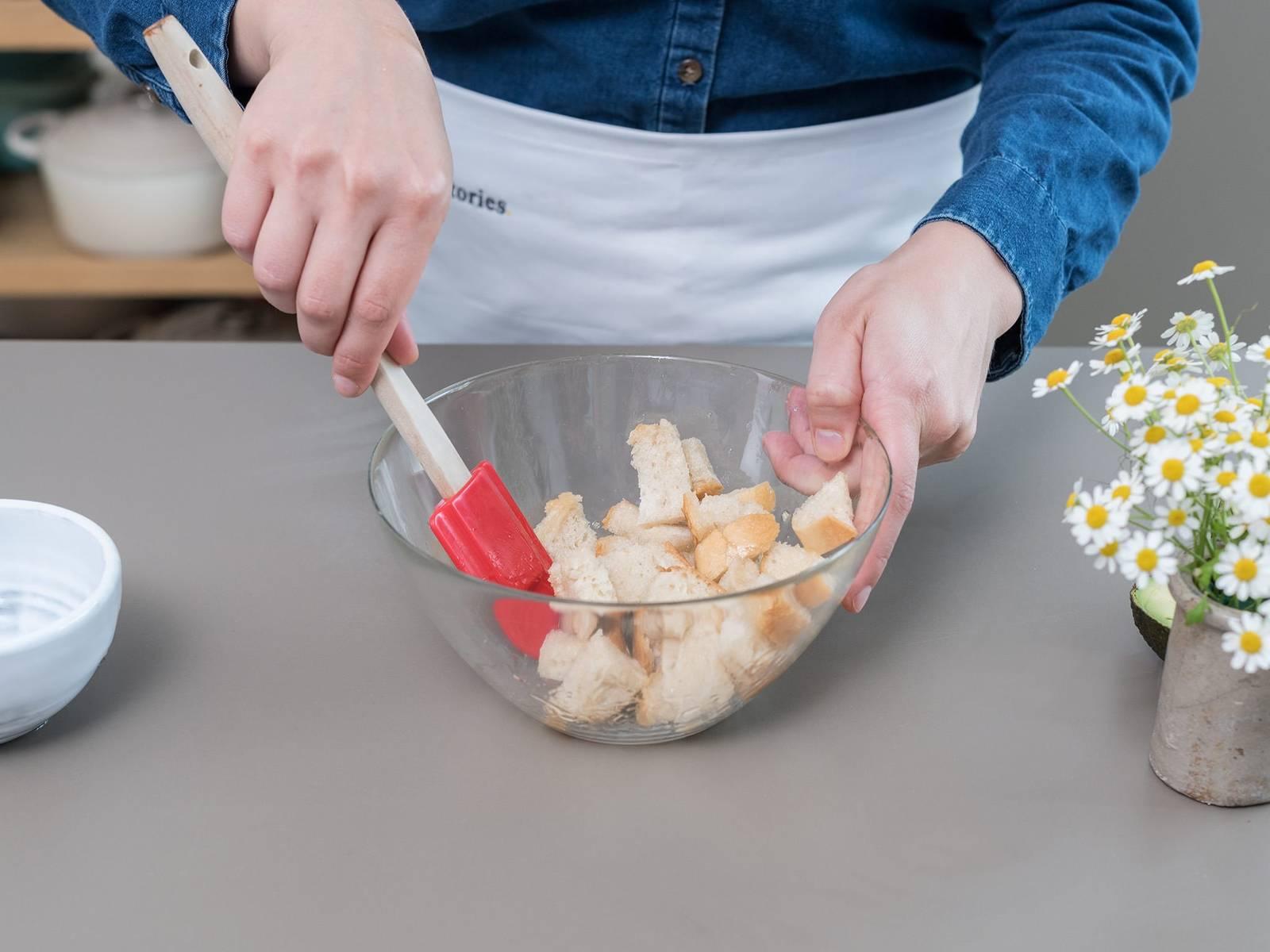 将面包切丁,将椰油倒在面包丁上,直至所有面包都均匀地浸泡到油里。