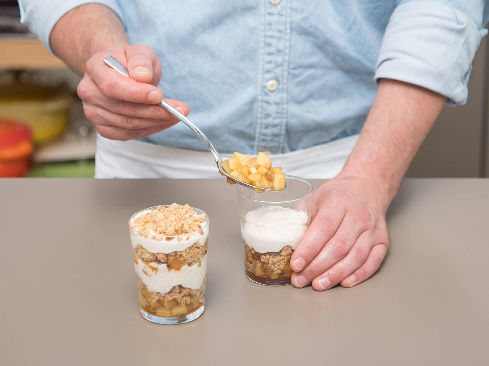 Das Dessert in Gläser schichten. Mit einer Schicht karamellisierten Apfelstückchen beginnen, Streusel darauf verteilen und Joghurtcreme darüber geben. Noch einmal mit allen drei Schichten wiederholen. Zum Schluss noch ein paar Streusel und Apfelstücken auf der Joghurtcreme verteilen. Bis zum Servieren in den Kühlschrank stellen. Guten Appetit!