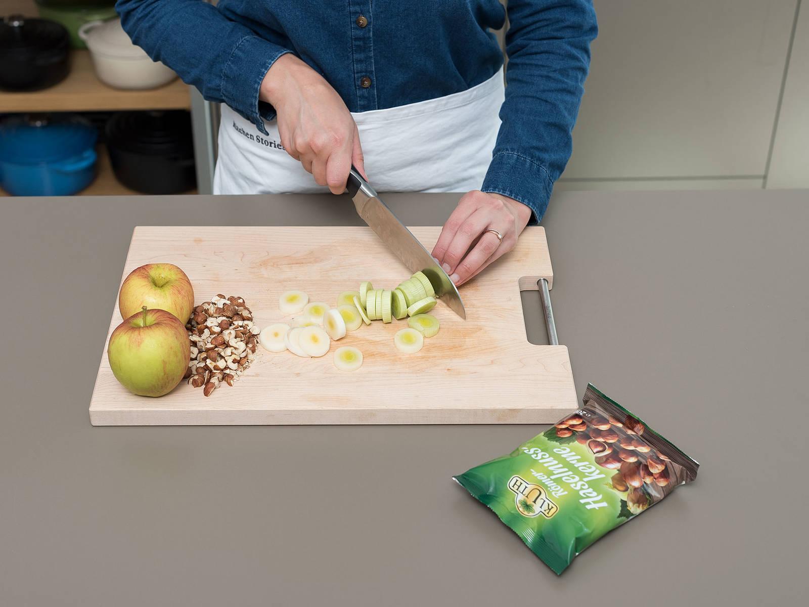 将烤箱预热至200℃。清洗韭葱,切成小段。苹果去核并切丁。榛子剁碎后置于一旁。将鸡蛋和酸奶油搅打混合,加盐与胡椒调味。