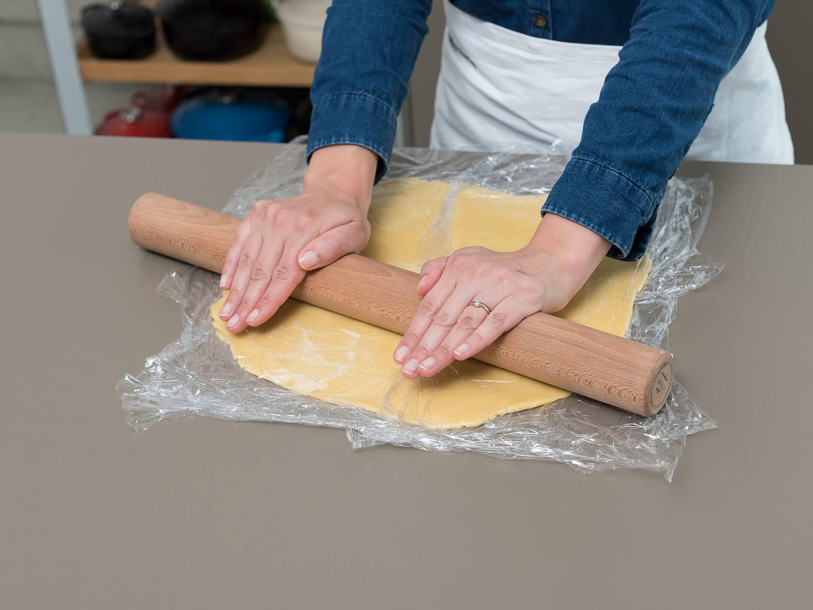 将乳蛋饼面团夹到两片塑料膜中,擀成直径约为28厘米的大圆形。