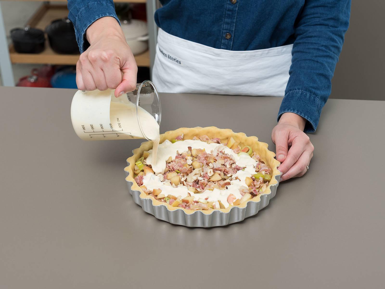 润滑馅饼盘,将面团放入盘中。轻轻将面皮均匀压入馅饼盘的边边角角,贴合盘壁。放入培根、韭葱和培根。撒上半份榛子,倒入鸡蛋混合物。