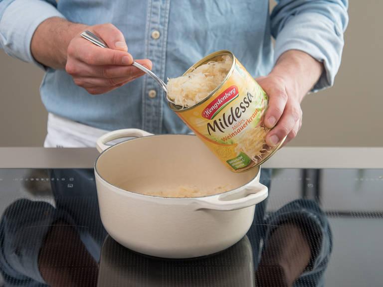 Für das Sauerkraut Zwiebel schälen und fein würfeln. Das restliche Butterschmalz in einem Topf bei mittlerer Hitze schmelzen und Zwiebelwürfel ca. 2 Min. anschwitzen. Sauerkraut und Weißwein dazugeben und ca. 5 Min. einköcheln lassen. Lorbeerblätter, Wacholderbeeren und restliche Rinderbrühe dazugeben. Mit Salz und Pfeffer würzen. Hitze reduzieren und mit Deckel ca. 30 Min. köcheln lassen.