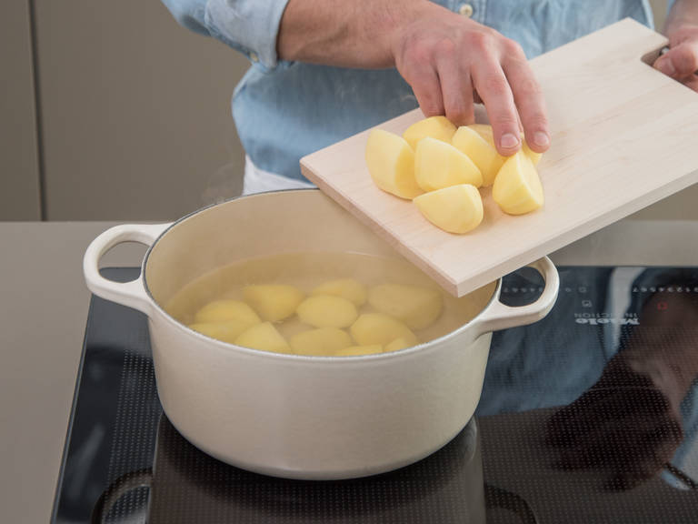 Peel and quarter potatoes. In a large pot, bring salted water to a boil, then add potatoes. Cook for approx. 20 min., or until potatoes are knife tender. Drain and keep warm.