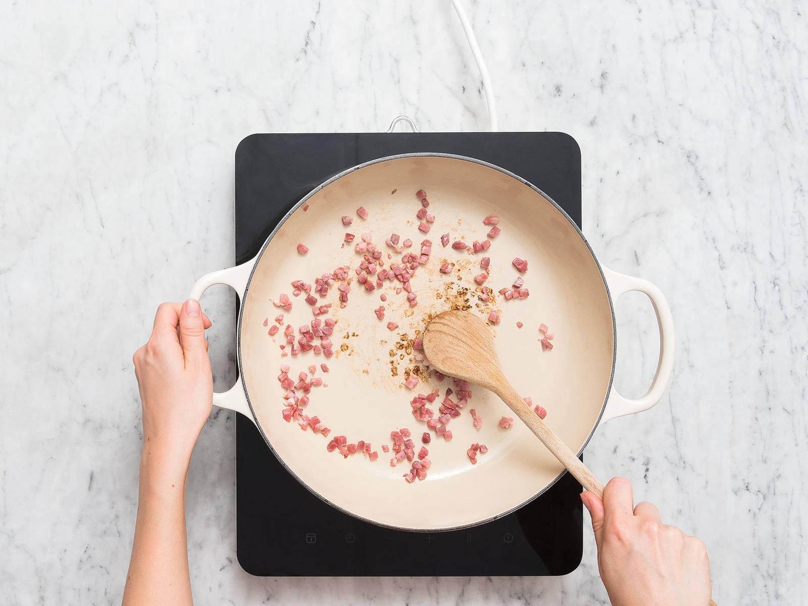 将烤箱预热至200℃。将石榴籽挖出,置于一旁。欧芹和薄荷剁碎,置于一旁。清洗土豆,切成楔形。胡萝卜和洋葱削皮后切成四瓣。在一个大耐热锅中,中高火煎培根丁4-5分钟,或直至焦脆。从锅中倒出,置于一旁。