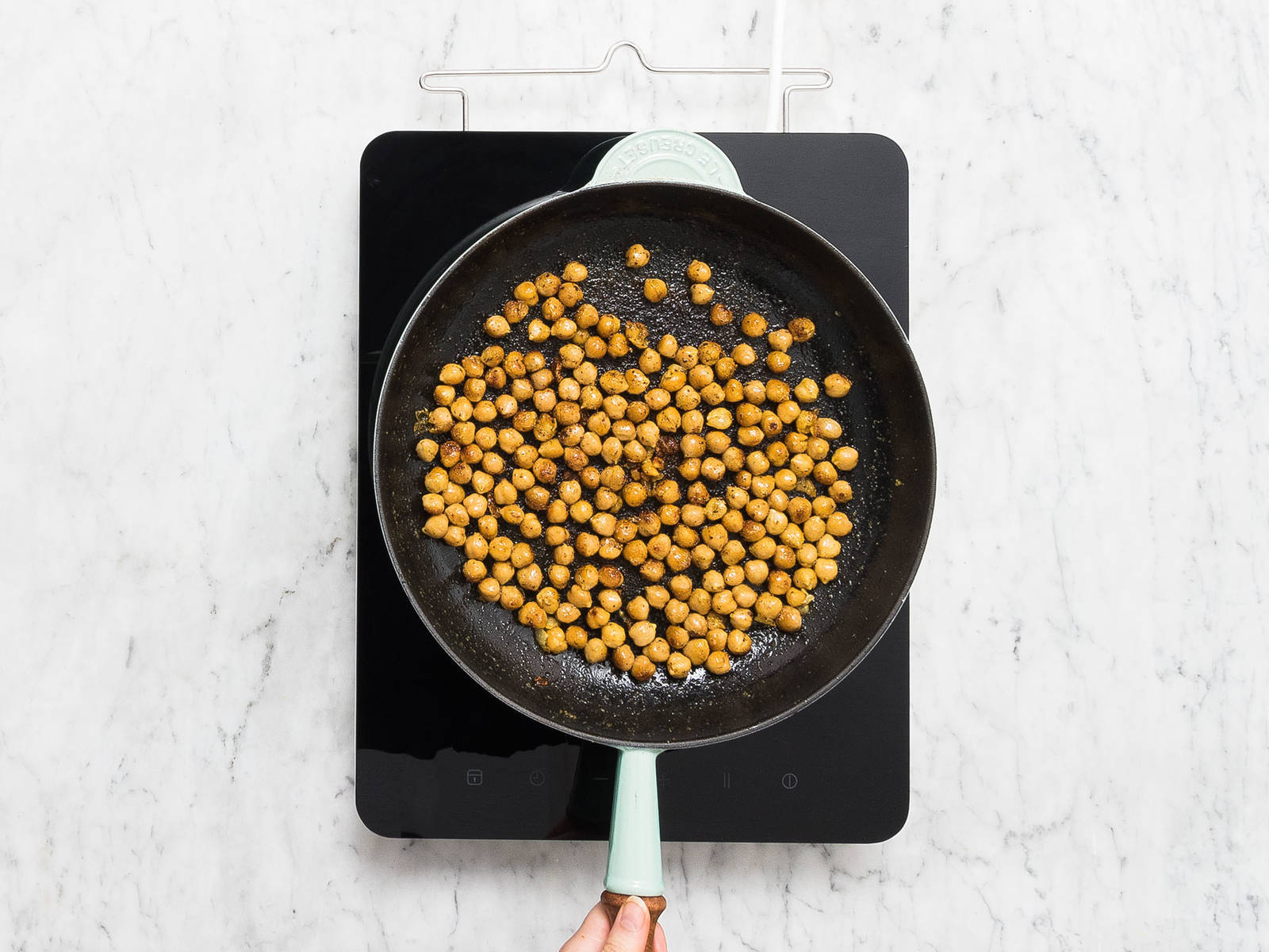 Rinse chickpeas until water runs clear, then pat dry. In a large bowl, mix chickpeas, curry powder, olive oil, and garlic powder together and season with salt and pepper. Heat a frying pan over medium-high heat and fry chickpeas for approx. 5 min., or until golden brown. Remove from pan and set aside.