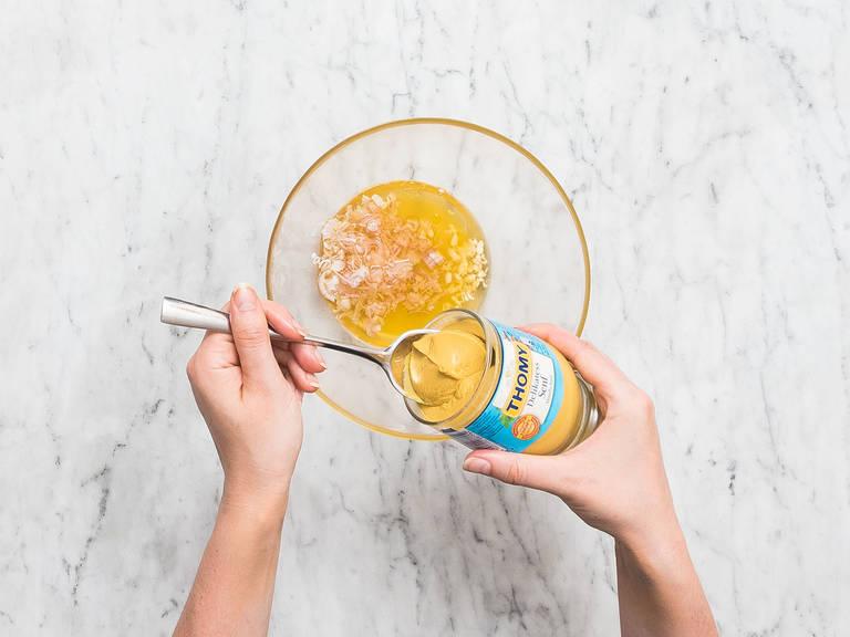 Orangensaft in einen kleinen Topf geben und bei mittlerer Hitze auf ca. ein Drittel reduzieren lassen. Zum Abkühlen beiseitestellen. Sobald der Orangensaft abgekühlt ist, mit Walnussöl, Apfelessig, gehacktem Knoblauch, Schalotte und Senf in einer Schüssel vermengen. Mit Salz und Pfeffer abschmecken.