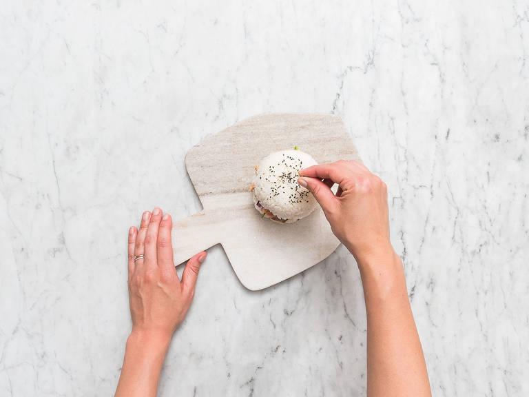 Sushireis aus einer Schüssel nehmen, auf einen Servierteller legen und Frischhaltefolie entfernen. Mit Gurkenscheiben, Sushi-Ingwer und Lachs-Mischung belegen. Avocado- und Rotkohlscheiben, sowie Wasabi-Mayonnaise darauf verteilen. Eine zweite Schüssel Sushireis als Burgerbrötchen darauf setzen und mit schwarzem Sesam bestreuen. Guten Appetit!