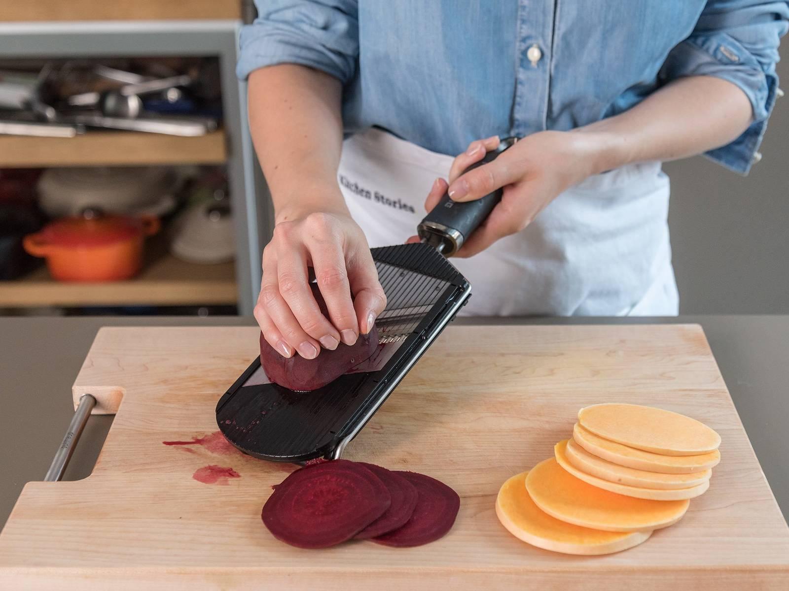Backofen auf 180°C vorheizen. Butternusskürbis und rote Bete mit einem Küchenhobel in feine Scheiben hobeln und diese auf einem Backblech verteilen. Walnüsse grob hacken.