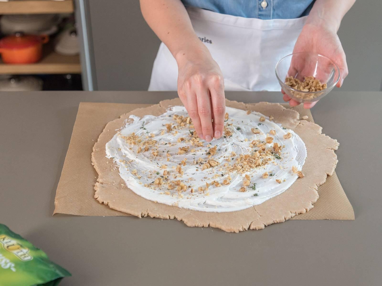 Teig aus dem Kühlschrank nehmen und auf Backpapier geben. Mit einem Nudelholz etwa 34 cm breit ausrollen. Ziegenkäse darauf verteilen, dabei einen etwa 4 cm breiten Rand auslassen und die Walnüsse darüber streuen.