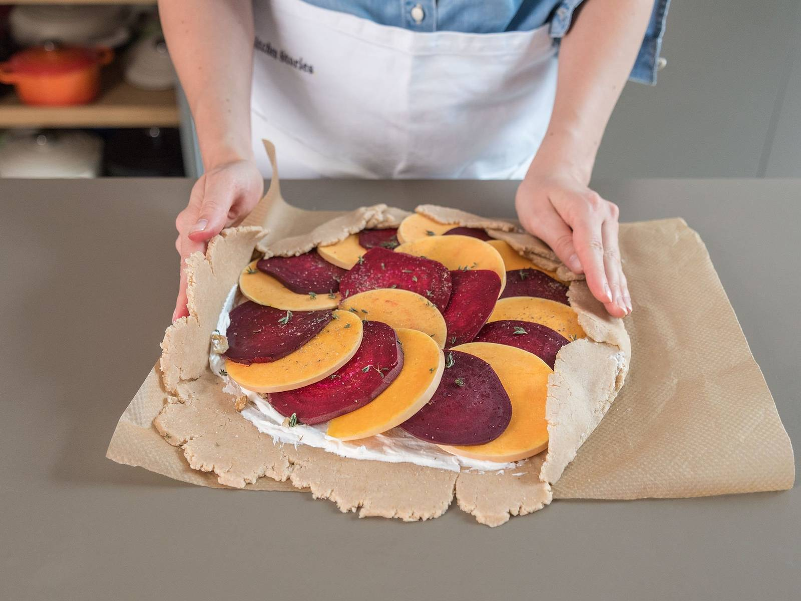 Pluck thyme leaves from stems and sprinkle half over the dough. Assemble the squash and beetroot slices over the goat cheese and sprinkle remaining thyme and salt and pepper over everything. Carefully fold over edges of dough.
