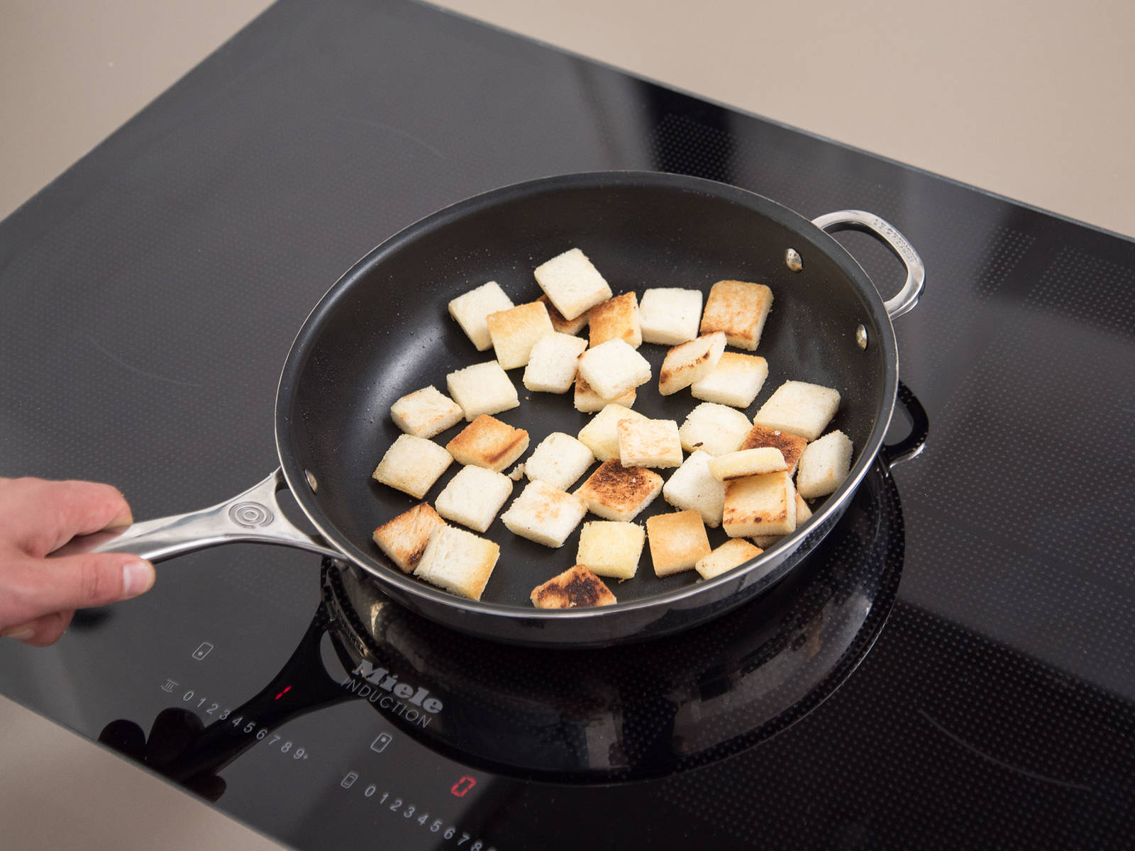 将香葱剁碎,然后和奶油奶酪一起放入碗中。搅拌混合,撒盐与胡椒调味。置于一旁。将白面包切成边长约2厘米的方块。在煎锅中,中高火加热橄榄油。煎面包5分钟,或直至面包变成金黄色。从煎锅中取出,置于一旁。