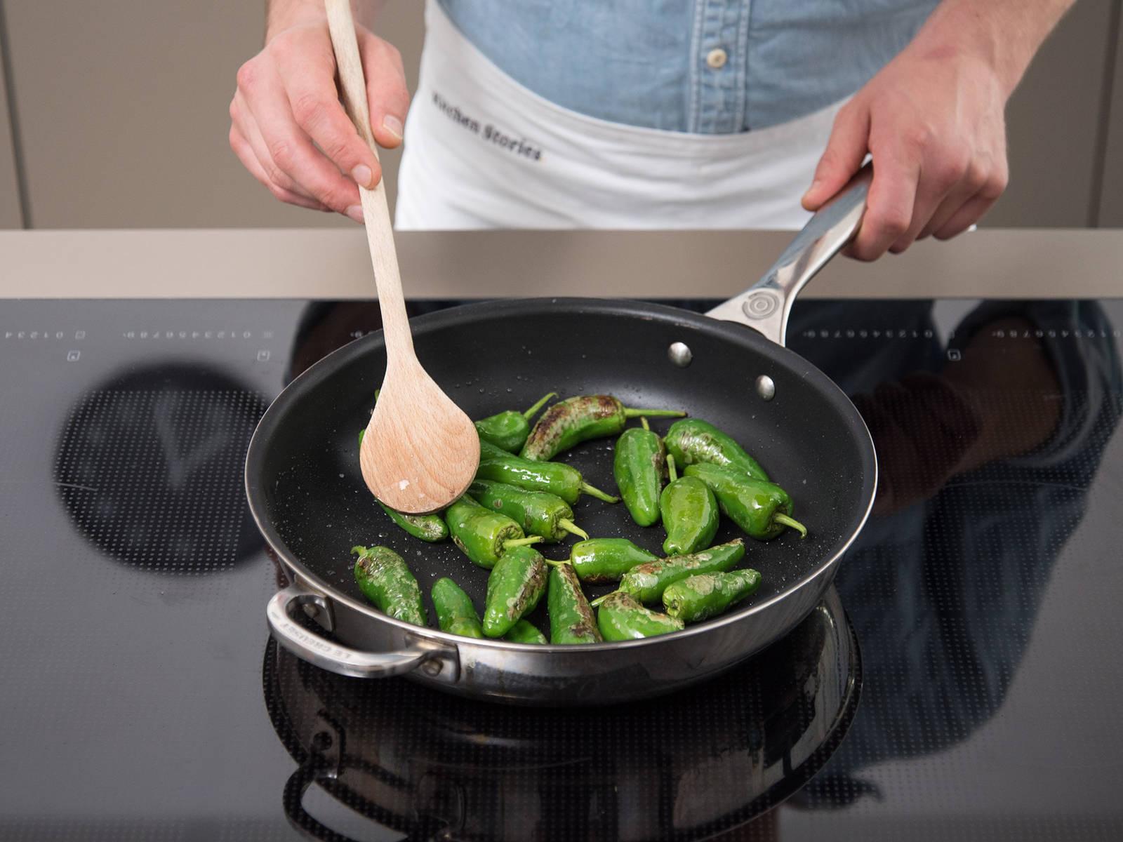 将帕德龙辣椒放入同一煎锅中,中高火煎2-3分钟,直至辣椒稍微烧焦。