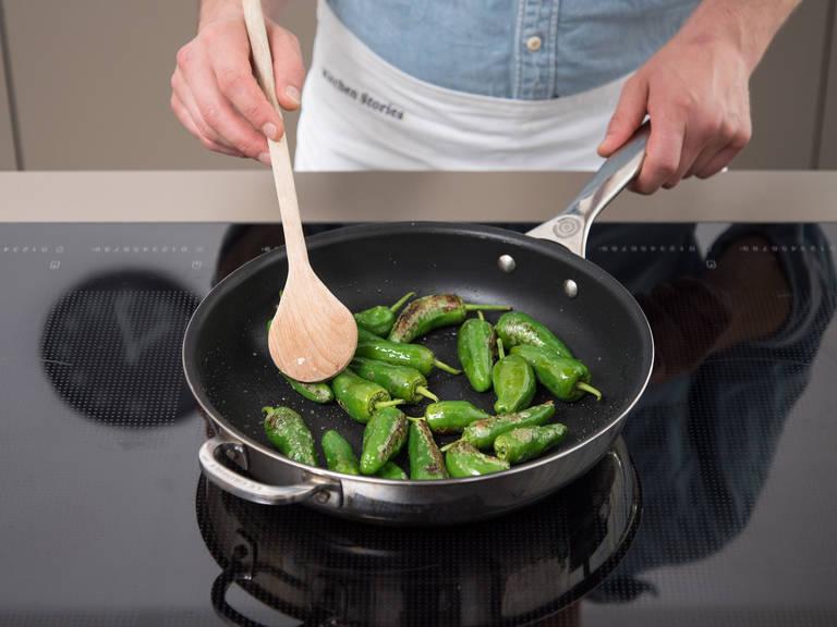 Pimientos de Padrón in die gleiche Pfanne geben und ca. 2 - 3 Min. bei mittlerer bis hoher Hitze anbraten bis sie geröstet sind.